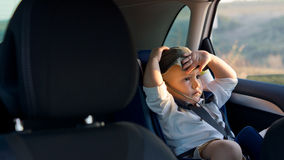 Young boy sitting in a baby seat. Young boy sitting in a baby or child seat in the rear of a car in sunshine with his hand to his head Royalty Free Stock Images