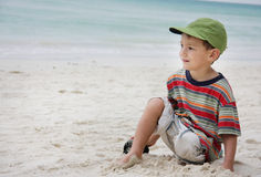 Young boy sitting on beach Stock Image