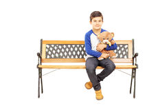 Young boy sitting on bench and holding teddy bear. Isolated on white background royalty free stock image