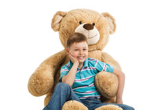 Young boy sitting at a big teddy bear Royalty Free Stock Photography