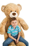 Young boy sitting at a big teddy bear isolated Stock Image