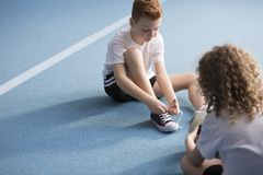 Young boy tying shoelaces. Young boy sitting on a blue floor and tying the shoelaces before physical education classes Royalty Free Stock Image