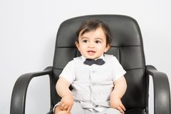 A young boy sitting on business chair presents himself as a businessman. Young boy sitting on business chair presents himself as a businessman Stock Photography