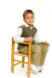 Young boy sitting in chair. Young boy sitting on a wooden chair.  Isolated against a white background Royalty Free Stock Photography