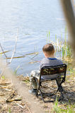 Young Boy Sitting on Chair and Holding Fishing Rod Stock Images