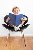 Young boy sitting in a chair reading a book Royalty Free Stock Photos