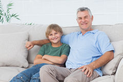 Young boy sitting on the couch with grandfather Royalty Free Stock Image