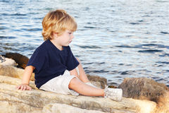 Young boy sitting by the edge of a lake Royalty Free Stock Photos