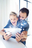 Young boy sitting with father at the table and using pc tablet in modern loft.Childhood dreams icons concept.Vertical Royalty Free Stock Photo