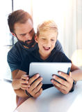 Young boy sitting with father at the table and using pc tablet in modern loft. Vertical, blurred background. Sunlights effect. Stock Photos