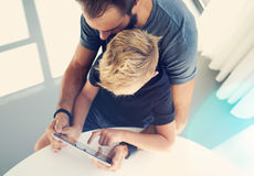 Young boy sitting with father and touching screen of pc tablet in sunny modern loft. Horizontal, blurred background. Top view,sunl Stock Images
