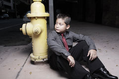 Young boy sitting by a fire hydrant Stock Image