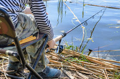 Young boy sitting fishing at a lake Stock Photography