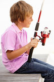 Young boy sitting with fishing rod Royalty Free Stock Photos