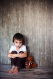 Young boy, sitting on the floor with his teddy bear, sad Stock Images