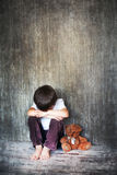 Young boy, sitting on the floor, teddy bear next to him, crying Stock Image