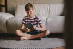 Boy playing online game on tablet at home stock photography