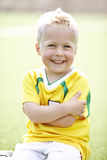 Young boy sitting on football field Royalty Free Stock Photo