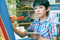 Young boy sitting in front of easel painting a fish, holding a brush in hand. Boy is getting ready to become an artist. Stock Photo