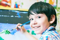 Young boy sitting in front of easel painting a fish, holding a brush in hand. Boy is getting ready to become an artist. Stock Image