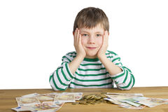 Young boy is sitting in front of money Royalty Free Stock Images