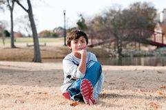 Young boy sitting in grass looking serious outdoors stock photo