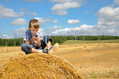 Young boy sitting on haystack with phone Stock Photo