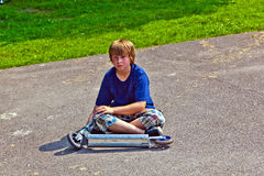 Young boy sitting with his scooter Stock Images