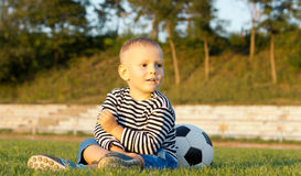 Young boy sitting with his soccer ball Stock Photo
