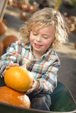 Young Boy Sitting and Holding His Pumpkin at Pumpkin Patch Stock Photography