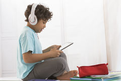 Young boy sitting at home, listen to music and royalty free stock image