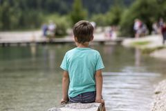 Young boy sitting by lake Stock Images