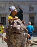 A young boy sitting on a lion statue in Venice stock photo
