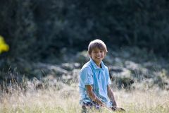 A young boy sitting in long grass, smiling Stock Photo