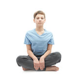 Young boy sitting in a lotus position Royalty Free Stock Photography