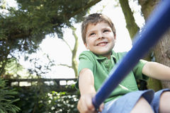 Young Boy Sitting On Monkey Bars Royalty Free Stock Photo