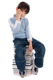 Young boy sitting over tower of books. On white background stock photos