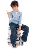 Young boy sitting over tower of books. On white background royalty free stock photography