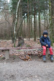Young boy sitting on a rustic wooden bench. In woodland staring down at the ground as he waits for someone stock photo