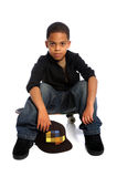 Young Boy Sitting on Skateboard. Young African American boy sitting on skateboard isolated over white Royalty Free Stock Photography