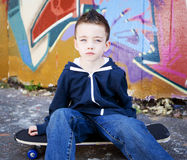 Young boy sitting on skateboard Royalty Free Stock Photos