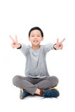 Young boy sitting and smiles over white. Young asian boy sitting and smiles over white background stock images