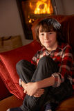 Young Boy Sitting On Sofa By Cosy Log Fire Royalty Free Stock Images