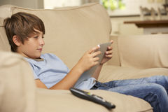 Young Boy Sitting On Sofa At Home Using Tablet Computer Royalty Free Stock Photography