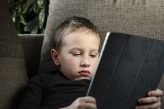 Young boy sitting on sofa in living room and watching cartoons on tablet. Portrait of a pre-school child using devices at home. Young boy sitting on sofa in royalty free stock photo