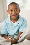 Young Boy Sitting On A Sofa, Text Messaging Royalty Free Stock Photos