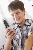 Young Boy Sitting On A Sofa Texting. On A Mobile Phone Royalty Free Stock Photo