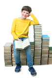 Young boy sitting on stacks of books and reading Royalty Free Stock Photos