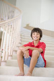Young Boy Sitting On A Stairwell At Home Royalty Free Stock Photography