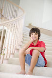 Young Boy Sitting On A Stairwell At Home stock photo